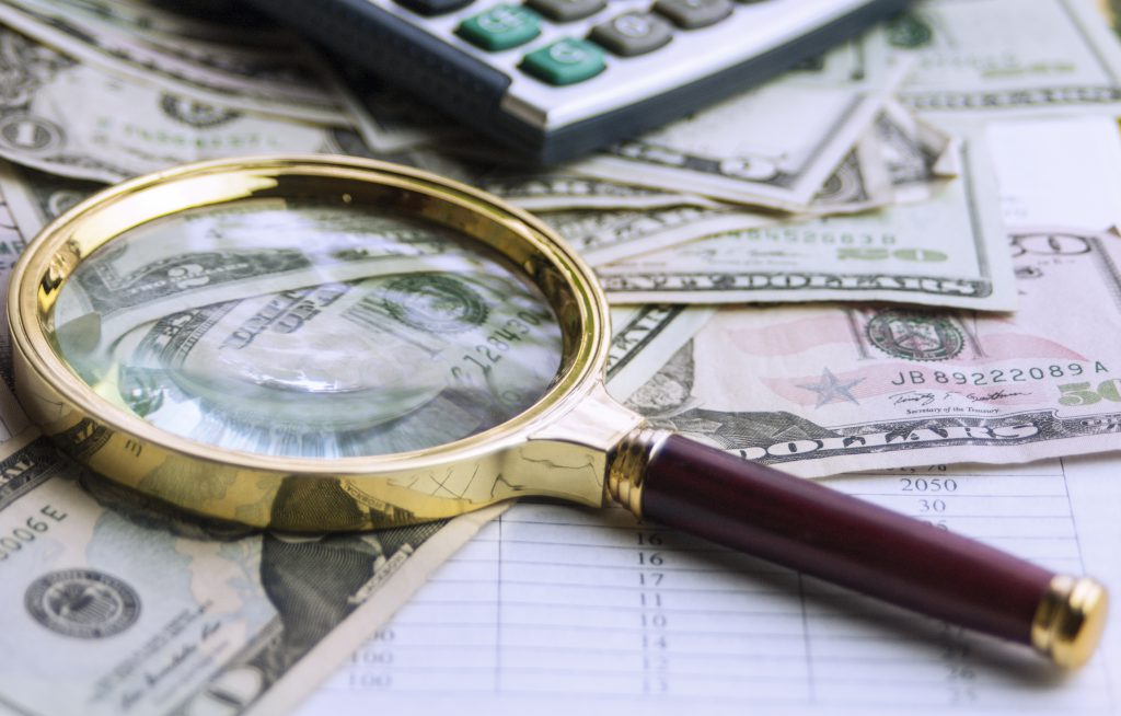 magnifying glass with us dollars